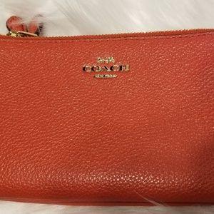 Orange leather Coach wristlet/wallet.